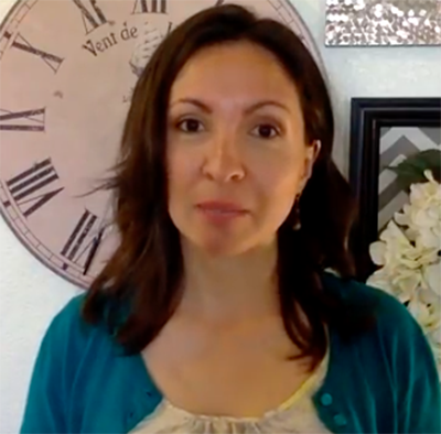 Photo of Dr. Morghan Velez wearing a teal cardigan standing in front of a large wall clock with flowers in the background