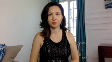Photo of Dr. Morghan Velez wearing a black shirt and standing in front of a window with teal curtains, white walls in the background, and a couch to the left