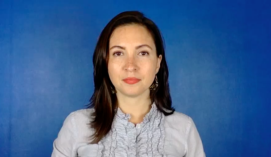 Photo of Dr. Morghan Velez wearing a gray, ruffled shirt in front of a blue background