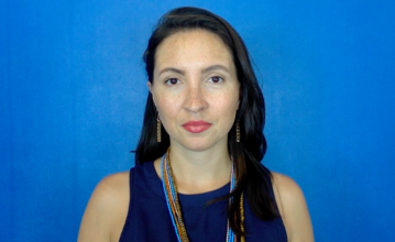 Photo of Dr. Morghan Velez wearing a blue shirt and standing in front of a blue background