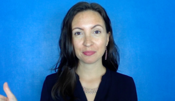 Photo of Dr. Morghan Velez wearing a black shirt and standing in front of a blue background