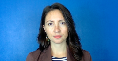 Photo of Dr. Morghan Velez wearing a brown suit jacket in front of a blue background
