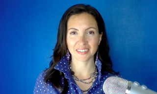 Photo of Dr. Morghan Velez wearing a blue polka dot collared shirt standing in front of a blue background with a microphone in front of her