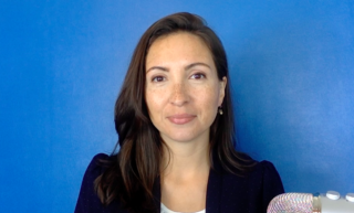 Photo of Dr. Morghan Velez wearing a black suit jacket, smiling, and standing in front of a blue background