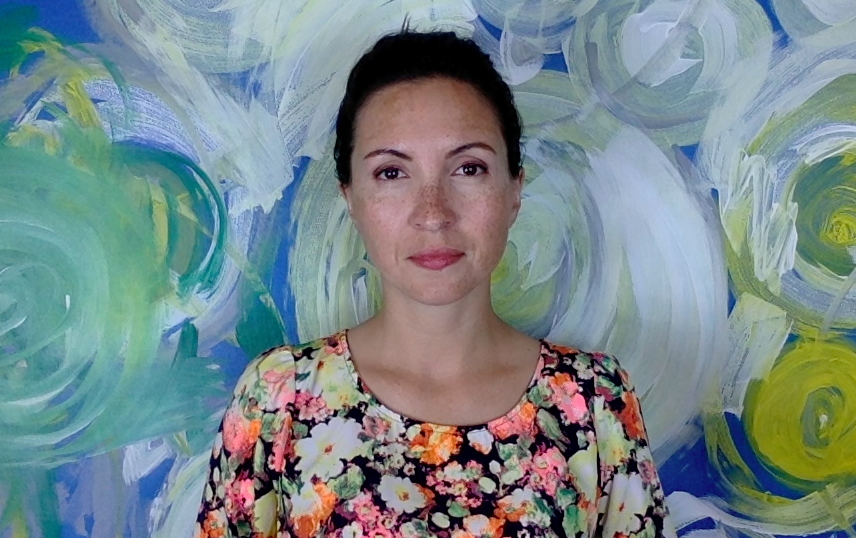 Photo of Dr. Morghan Velez wearing a floral print shirt with her hair pulled up standing in front of a colorful painting